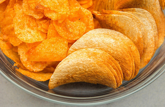 How bad are processed foods? - Glass bowl with crisps and pringles