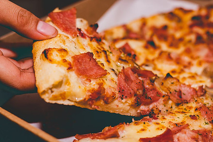 How long can leftovers stay in the fridge? - Person taking slice of pepperoni pizza