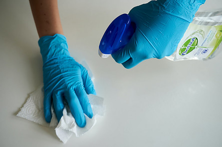 Organising food cupboards - gloved hands cleaning counter