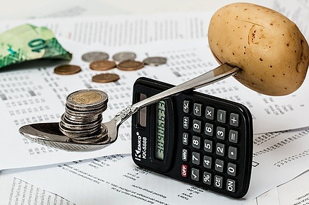 Best cheap healthy foods - scales cost of money versus food, spoon balancing money and potato on calculator