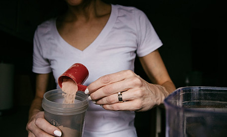 Best cheap healthy foods - woman pouring protein powder scoop into protein shaker