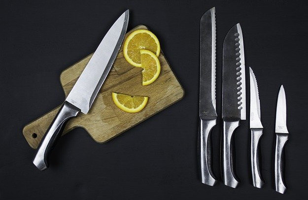 Healthy eating kitchen gadgets - set of stainless steel kitchen knives on chopping board