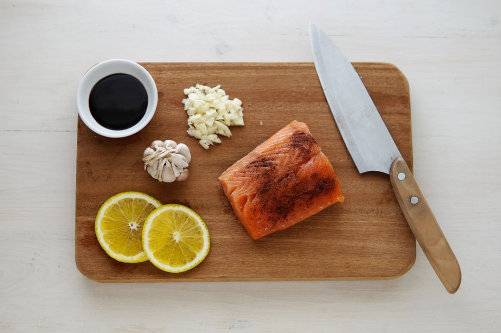 Healthy eating kitchen gadgets - wooden chopping board with salmon and chef's knife