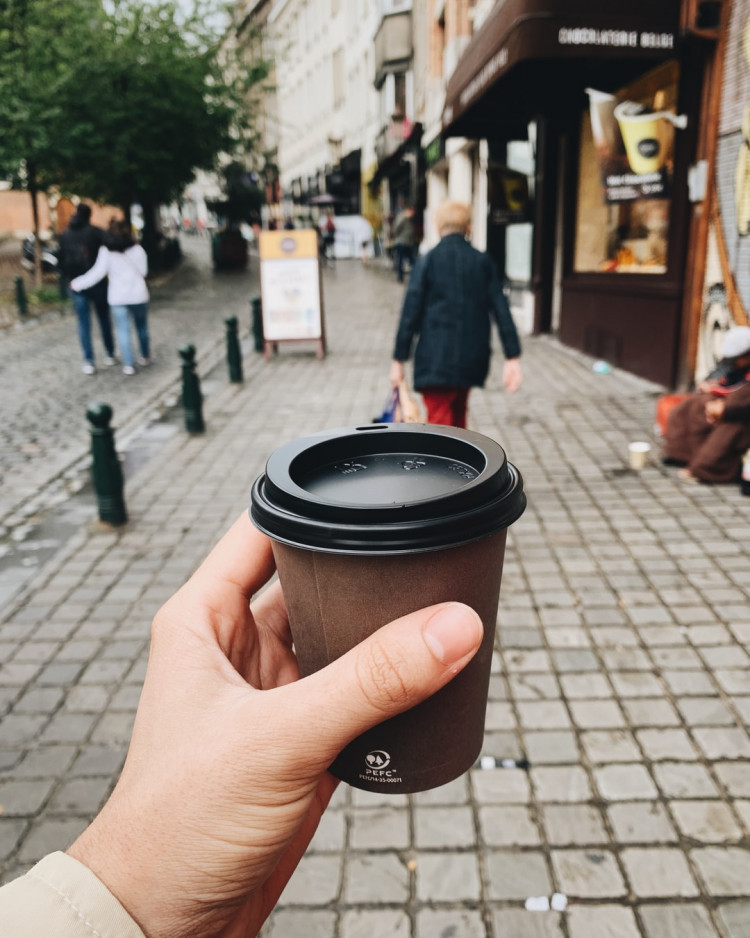 How to eat clean on the go - person holding disposable coffee cup on street