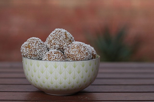 How to eat clean on the go - Protein balls with dessicated coconut in bowl on table