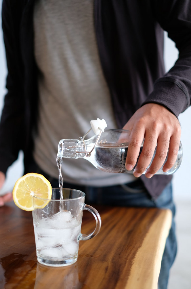 How to fight cravings for food - Man pouring water into glass mug