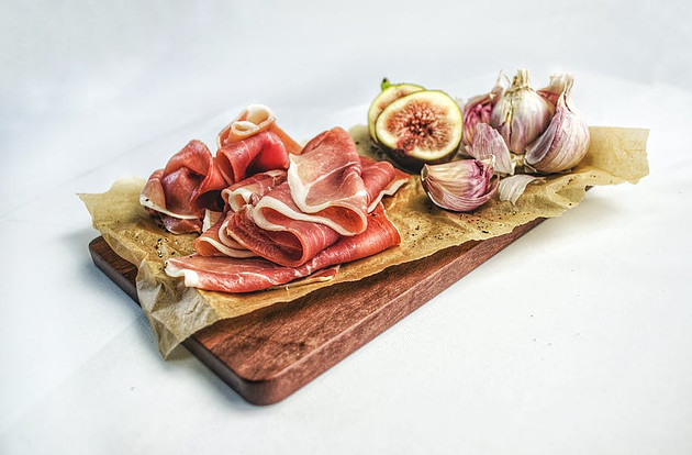 What foods should not be microwaved? - Parma ham sliced on chopping board