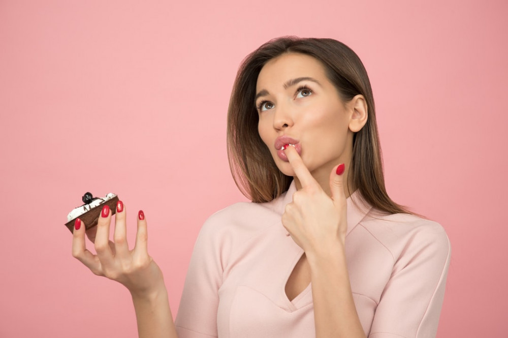 How to make a healthy dessert - Woman licking dessert from her finger while holding dessert