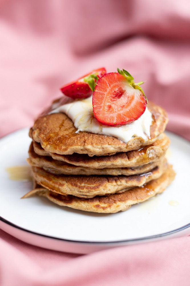 How to make pancakes healthy - Stacked pancakes topped with yoghurt and strawberries