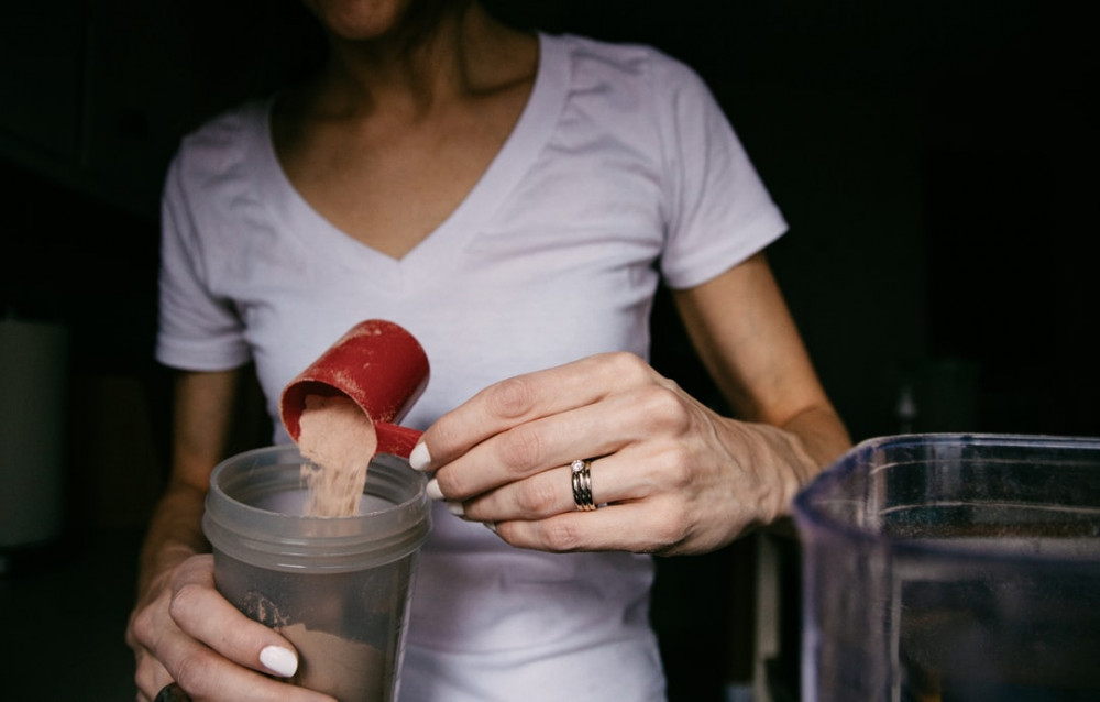 How to make smoothies healthy - Woman pouring scoop of protein powder into shaker