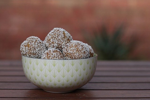 Best ways to use protein powder - Bowl of dessicated coconut protein balls