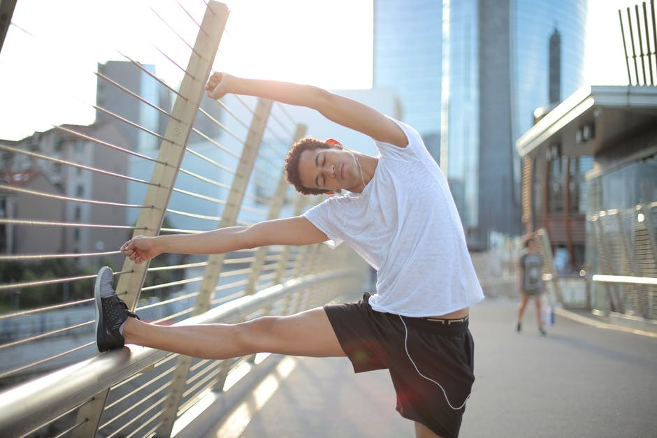Workout tops for men - Man stretching on bridge